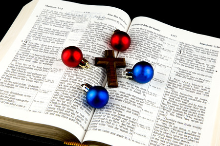 cross: Christmas decorations and wooden cross on Bible on black background Stock Photo