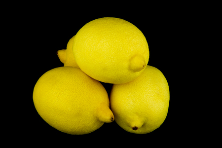 acidic: A pile of fresh lemons stacked against a black background