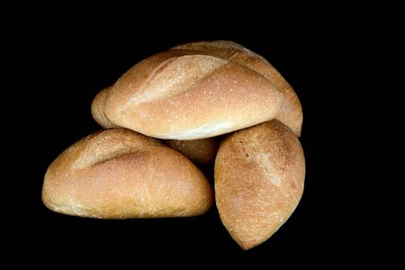 crusty french bread: Fresh baked bread rolls isolated against a black background
