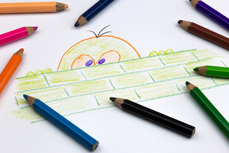 coloured pencils: A funny drawing and childs coloured pencils on white paper