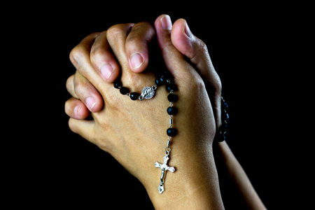 Asian woman hands praying with rosary and small silver crucifix