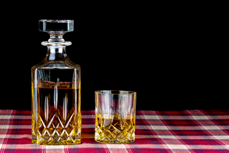 liqueurs: Whisky on tartan table cloth against a black background Stock Photo