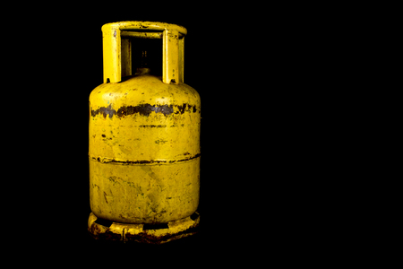 propane gas: A rusting propane gas tank isolated against a black background