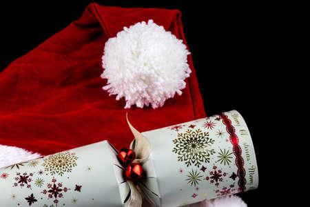 christian festival: Christmas santa hat and traditional Christmas cracker on black background Stock Photo