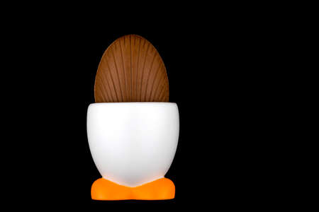 egg cup: Chocolate Easter egg in white egg cup isolated on black