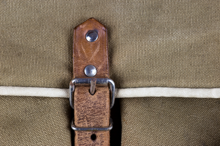Detail of buckle and leather strap on old canvas bag