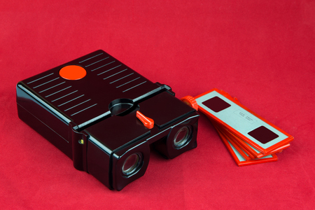 viewer: Vintage stereo slide viewer and slides on a red surface