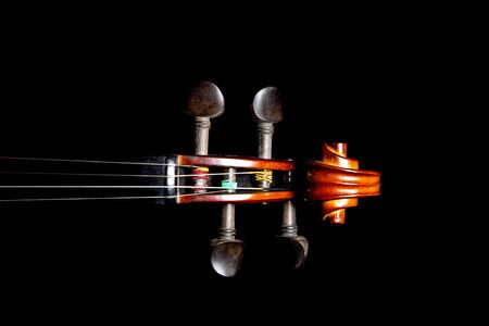 fiddles: Violin scroll peghead isolated against a black background Stock Photo
