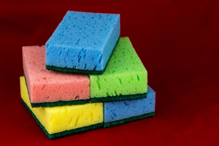 Household cleaning sponges stacked on a red cleaning cloth Banco de Imagens