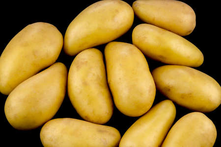Small organic potatoes isolated on a Black Background