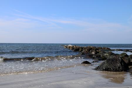 Rocky outcrop sand and sea at a coastal beach Stock Photo