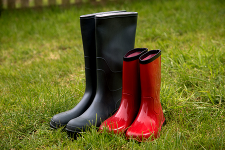 Green and red rubber boots on meadow grass