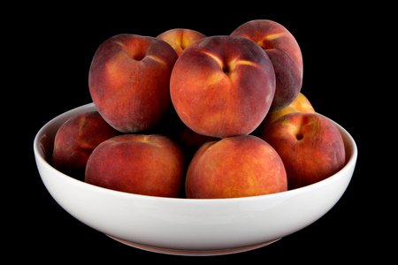 Peaches in a white bowl isolated on a black background