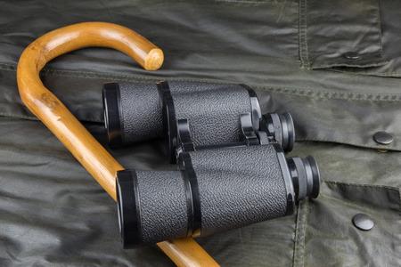 Binoculars and walking stick on a waxed outdoor coat