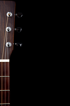 Partial view of peg head and neck of acoustic guitar isolated against a black background
