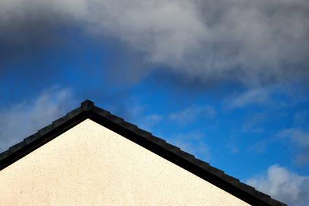 House roof apex against a blue cloudy sky