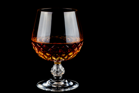 Brandy in a crystal glass isolated against a black background Reklamní fotografie