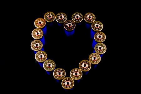 Twelve gauge shotgun cartridges upright on a black background in shape of a heart