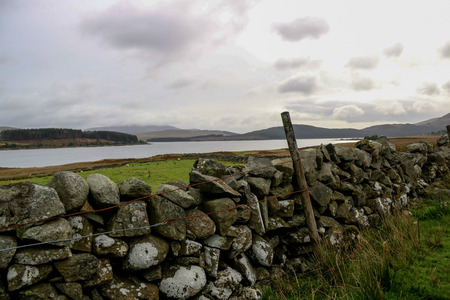 Autumn view of old stone wall and wire fence with Scottish loch behind