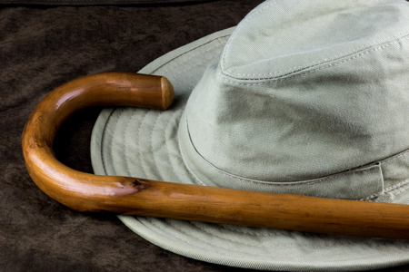 Brimmed hat and walking stick on an outdoor coat