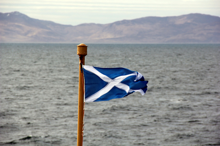Scottish Saltire flag blowing in the breeze on board ferry to Isle of Islay, Inner Hebrides, Scotland. Stock Photo