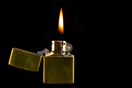 Well used brass lighter with flame isolated against a black background