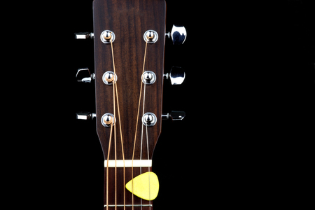 Acoustic guitar peg head and plectrum isolated on a black background