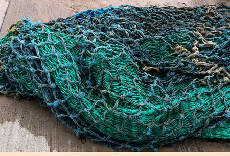 Old fishing nets piled at a coastal harbour