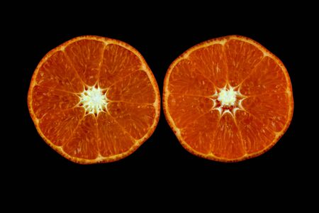 Cut orange halves isolated against a black Banco de Imagens