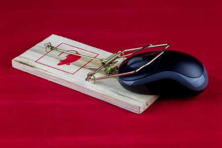 An old fashioned wooden rodent trap with computer mouse on a red background Foto de archivo