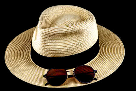 Straw Panama hat and sunglasses isolated against a black background