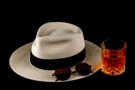 Straw Panama hat with drink and sunglasses isolated against a black background