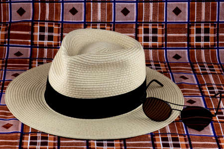 Straw Panama hat with sunglasses on a colourful beach sarong
