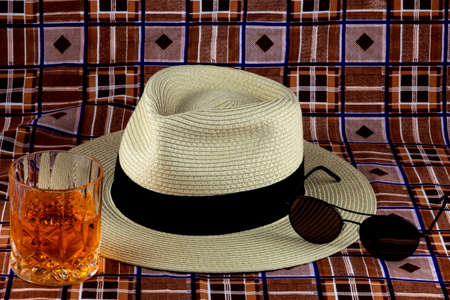 Straw Panama hat with drink and sunglasses on a colourful beach sarong