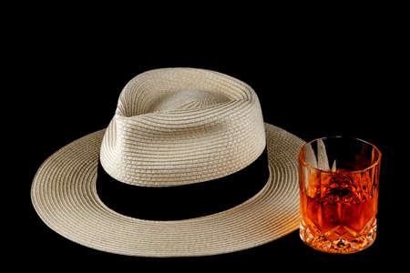 Straw Panama hat with drink isolated against a black background