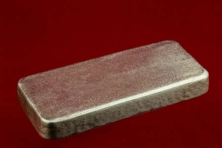 Solid silver ingot isolated on a red background