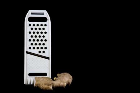 Mandolin food slicer with fresh ginger isolated on a black background Imagens