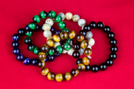 Stone bead jewellery bracelets on a red background Imagens