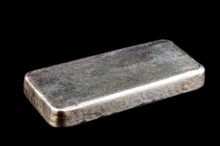 Solid silver ingot isolated on a black background Imagens