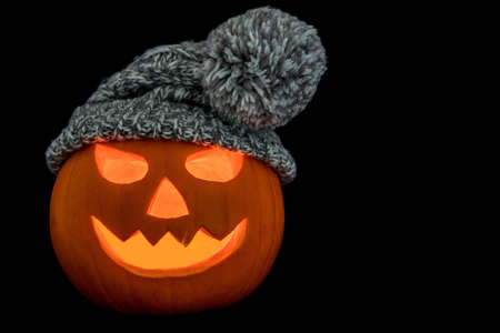 Carved halloween pumpkin wearing a woolly hat isolated on a black background 免版税图像