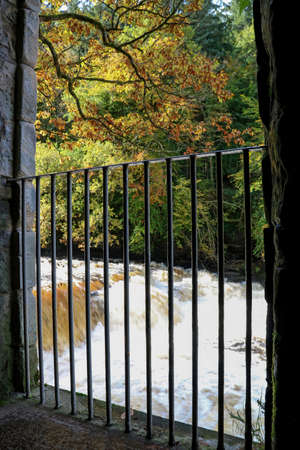 River rapids viewed through old steel handrail barrier