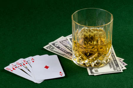Card game hand with US Dollars and whisky on a felt table top