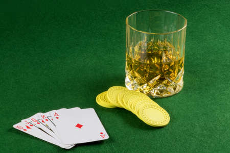 Card game hand with gambling chips and whisky on a felt table top