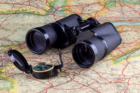 Binoculars and trecking compass on an old route map