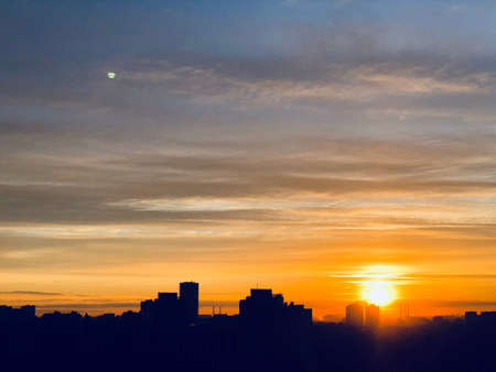City skyline, silhouette against sky with clouds, sun and moon on a sunset, dawn. City skyline, skyscraper silhouettes with sunset sky on the background 写真素材