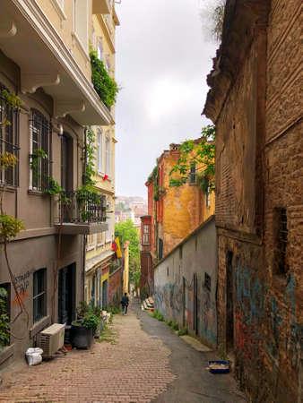 Leere nach unten gerichtete Seitenstraße von Istanbul, Türkei mit historischen Steingebäuden und Graffiti in den frühen Morgenstunden. Istanbul, Türkei Seitenstraße am frühen Morgen