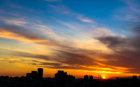 City skyline, silhouettes of buidings against dramatic sky in sunset, dawn, late evening hours. City skyline, skyscraper silhouettes with blue and orange sunset sky on the background 写真素材