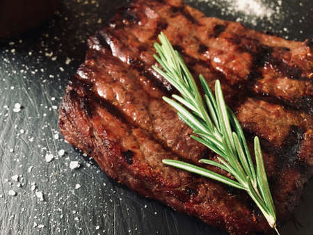 Grilled beef steak meat with rosemary on top served on black plate with sea salt