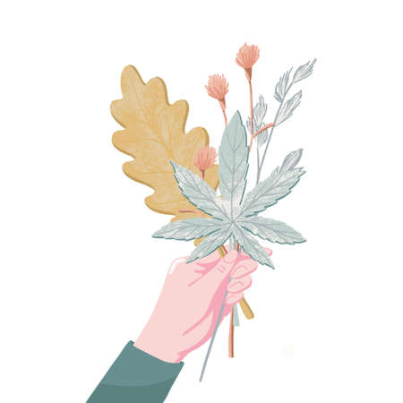 Female hand holding bouquet of fall, autumn leaves
