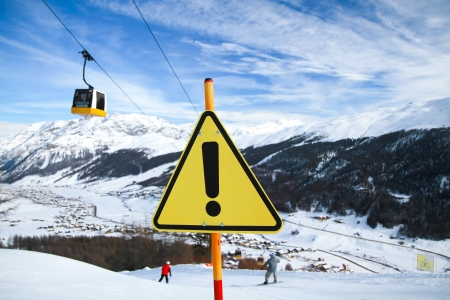 Yellow and black warning sign with gondola, 2 skiers and a mountain village in the background  photo